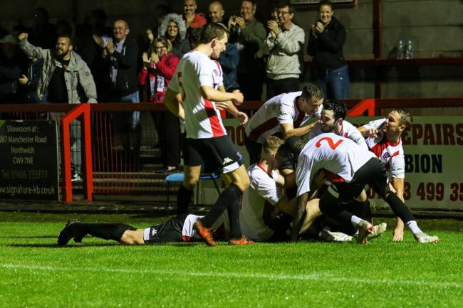 The magic of the moment as the pile-on commences in celebration of Danny McKenna's goal in Witton Albion's 1-0 defeat of Mickleover Sports. Picture: Karl Brooks Photography