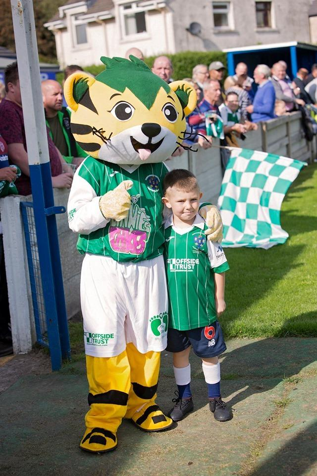 Tricky the Cat and a young fan enjoying the carnival atmosphere created by Northwich Victoria fans during the FA Cup clash with Lancaster City on Saturday. Picture: Angela Buckley