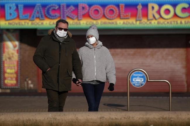 People wearing facemasks walking on Blackpool seafront