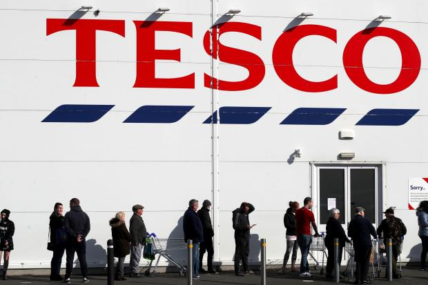 Northwich Guardian: People queue outside a Tesco Extra store in Madeley, Shropshire