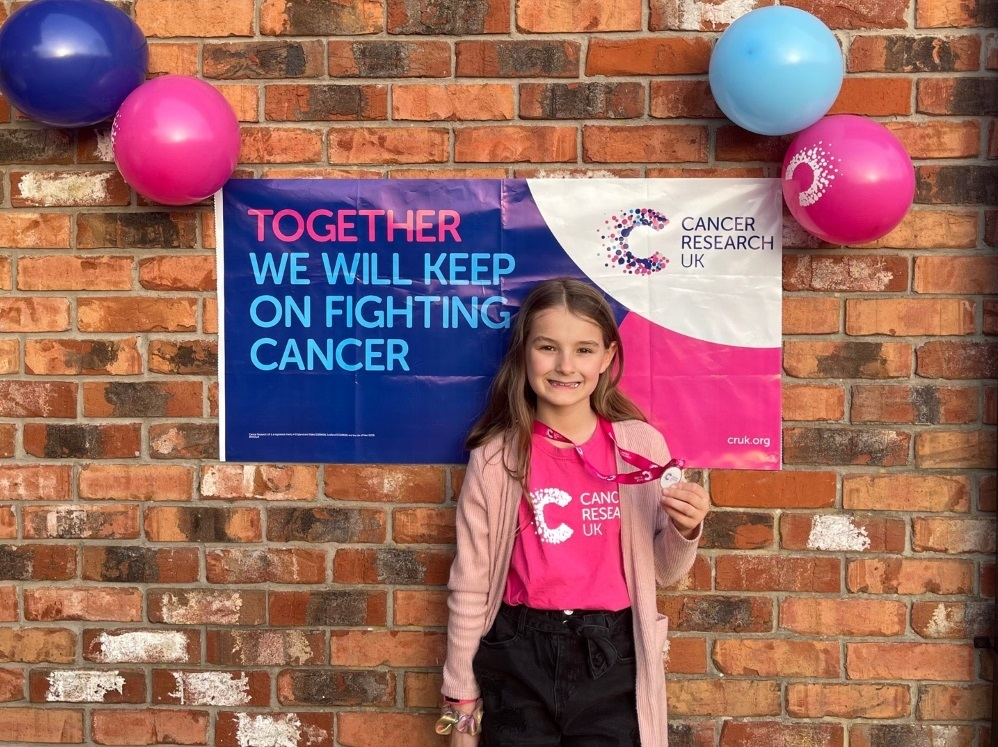Charley received a medal from Cancer Research UK for her incredible achievement