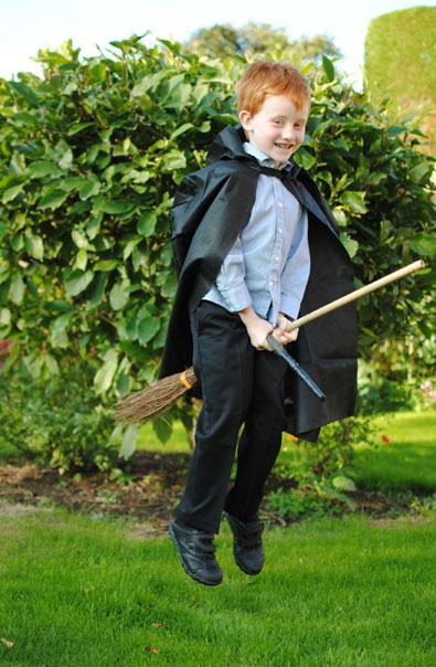 Five-year-old Alexander Quinton is flying across the garden, dressed as wizard Ron Weasley