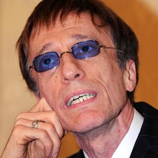 The family of Robin Gibb are keeping a bedside vigil as the singer remains in a coma