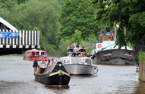 Town Bridge swings open as historic narrowboat Shad, which was built at Yarwoods in Northwich, the Princess Katherine and LS Lowry cruise past the James Jackson Grundy, moored at Barons Quay.