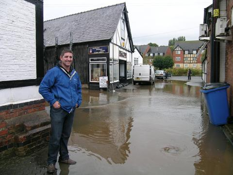 Paul Harris watches the floodwater approach Northwich Fireplace Centre.