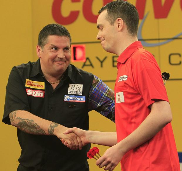 Gary Anderson, left, shakes Stuart Kellett's hand following Friday's first round encounter at the Cash Converters Players' Cham