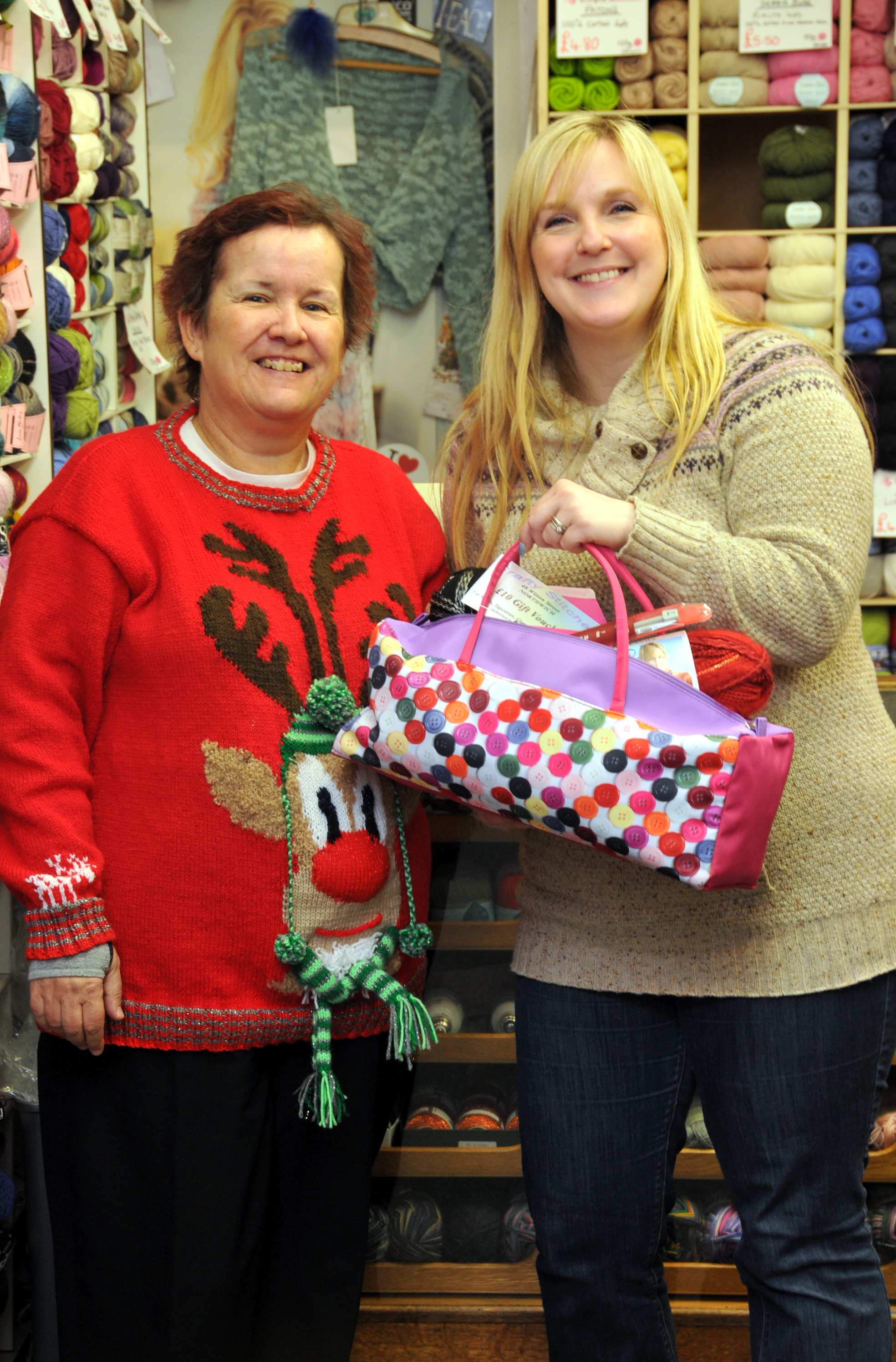 Sandra Graham, wearing her winning Christmas jumper, is awarded her prize of a £10 gift voucher, knitting bag and goodies worth £40 by Louise Hough, from Crafty Stitches.