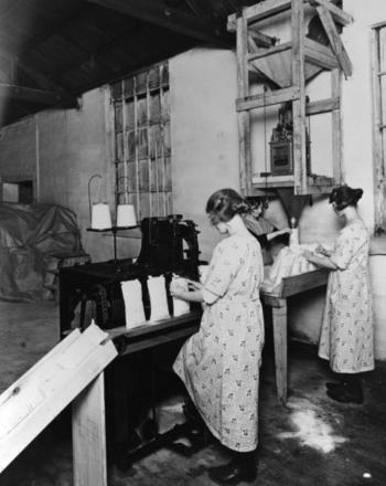 Machine Operators filing and fastening salt bags during the Great War. Photograph taken from the collection held at Weaver Hall Museum and Workhouse, in Northwich.