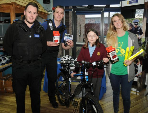 PCSOs Andy Taylor and Mark Howard with Sarah Daimond, from Sustrans, offer cycling safety goodies and advice to Georgina Burke, 10, from Hartford Manor Community Primary School.