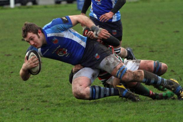 Harry Stubbs' progress is halted by a Hoylake tackler