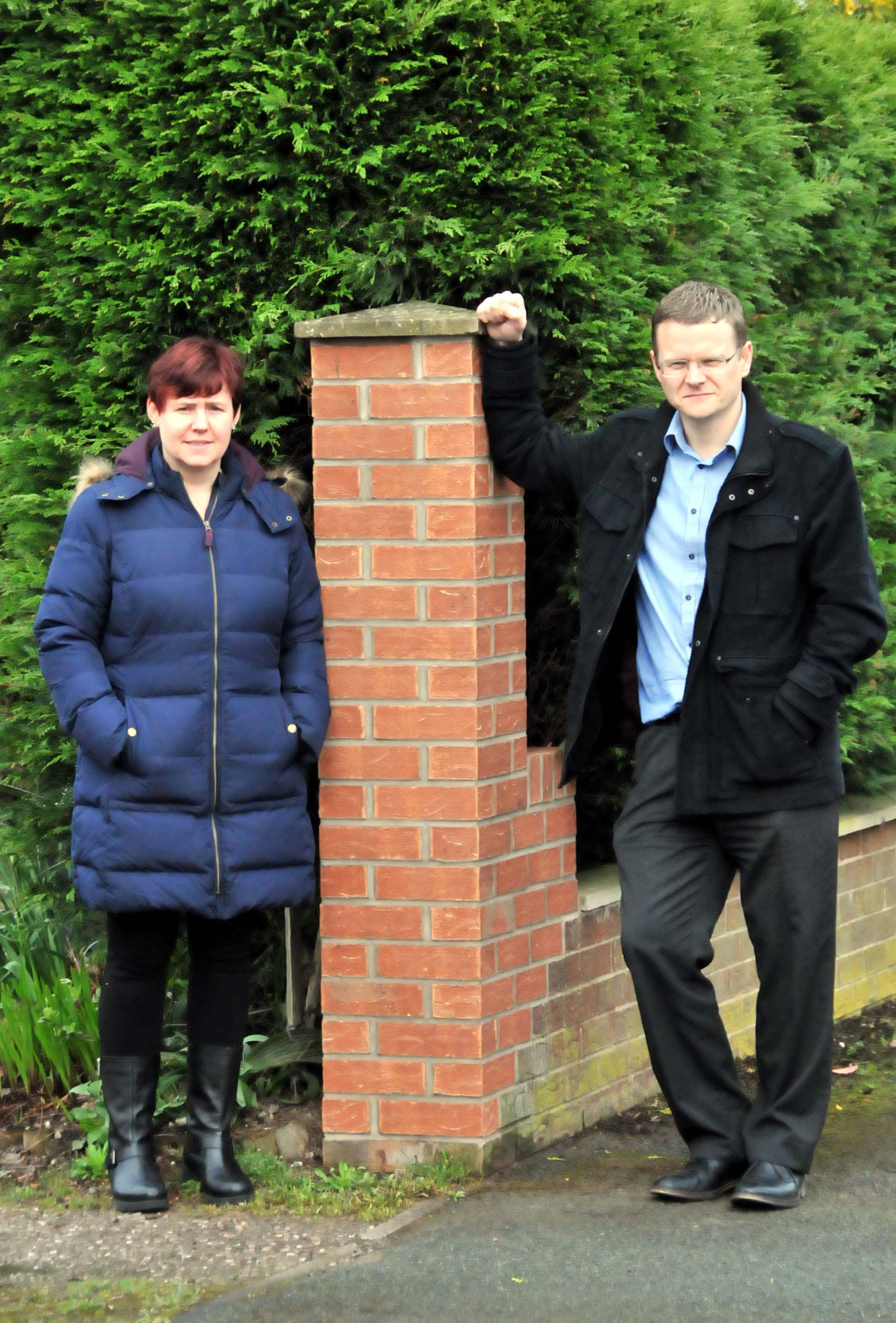 Mr and Mrs James next to the rebuilt gatepost