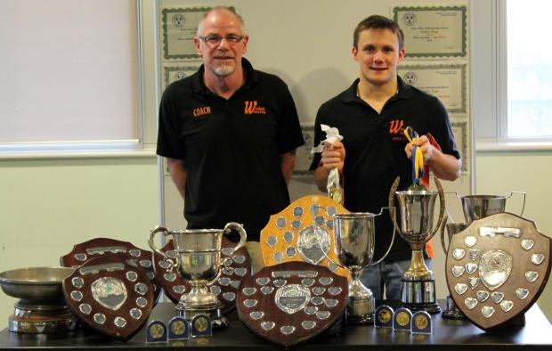 Ashley Hogg, right, shows off the silverware he won while representing Win