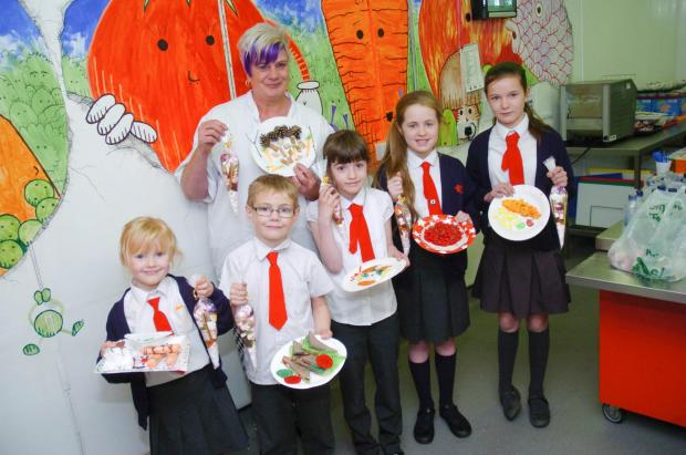 Catering manager Sarah Booth with children showing their winning plate designs. From left, Connie Shrieves, Luke Sayle, Katie Acton, Daisy Oultram, Robyn McGahemn. Trinity Mullen, who is not pictured, also won a prize. m141547.