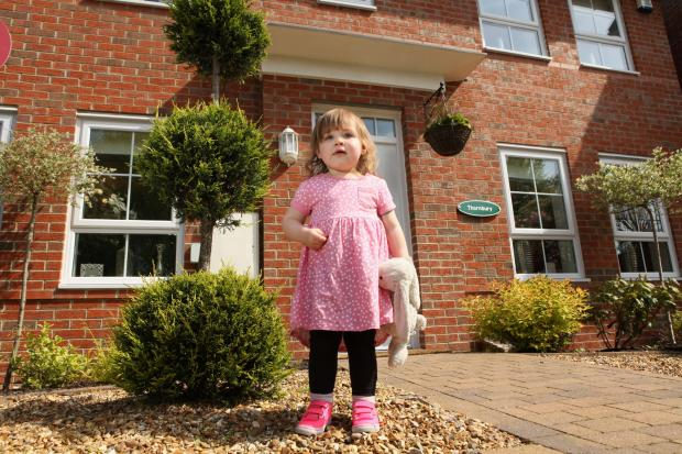 Isabella Wallsworth-Jones, two, outside one of the Barrett homes in Lostock.