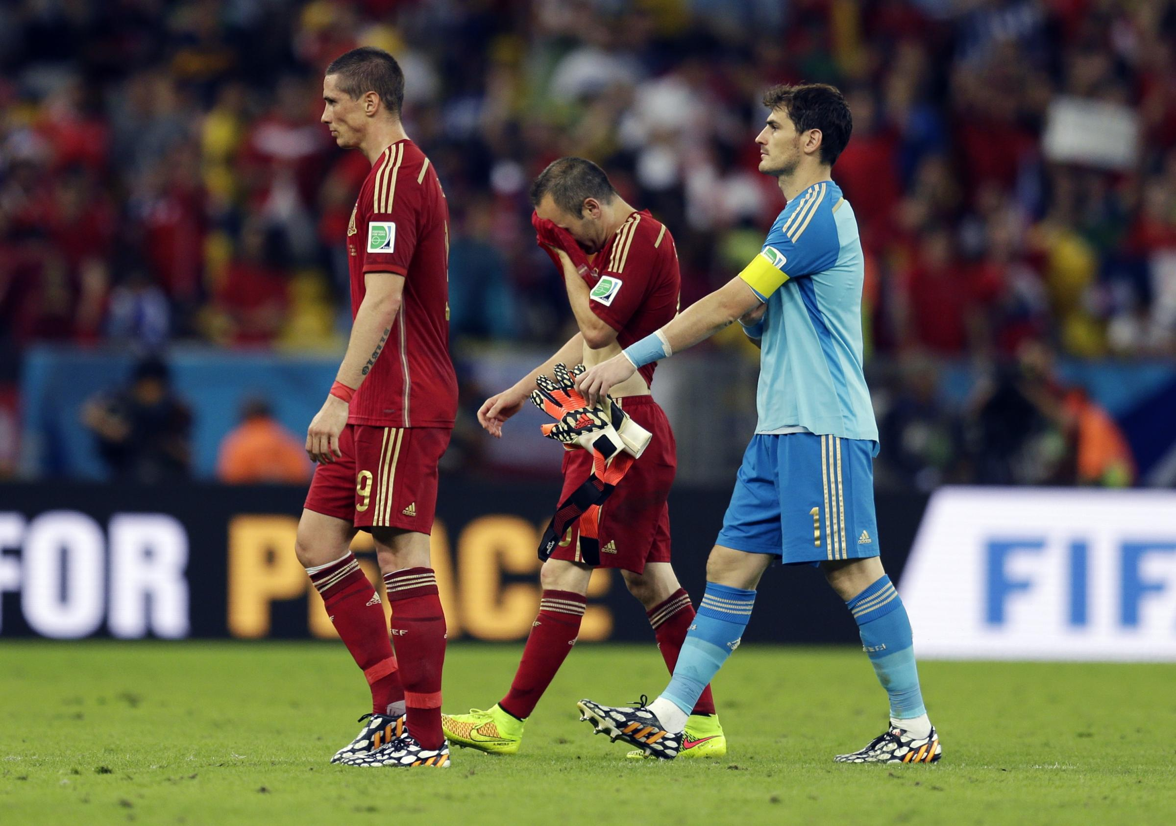 From left, Spain's Fernando Torres, Andres Iniesta and goalkeeper Iker Casillas walk off the pitch following their group B World Cup soccer match between Spain and Chile at the Maracana Stadium in Rio de Janeiro, Brazil