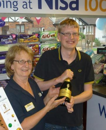 NISA Local owner Carole Ball presents the champagne to competition winner Thomas Russell