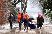 Children run through the snow to school in Great Budworth.