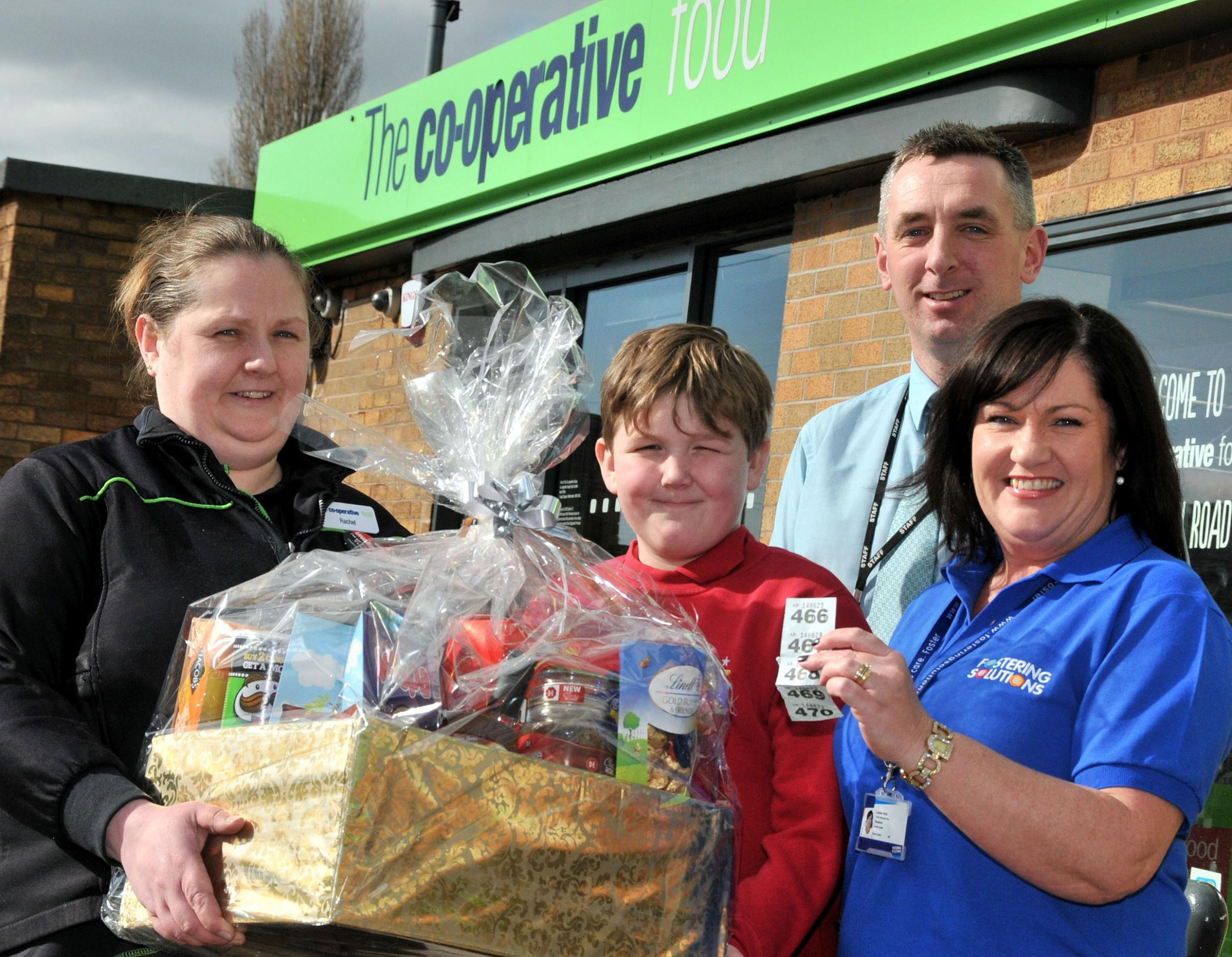 Ellis Lovell presents the hamper to Louise Reid, right, watched by Co-op manager Rachel Stanway and Rudheath Primary Academy principal Andrew Ross.