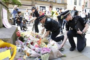 Officers lay flowers in St Ann's Square, Manchester, to mark the deaths that followed the explosion (© Martin Rickett/PA Wire)