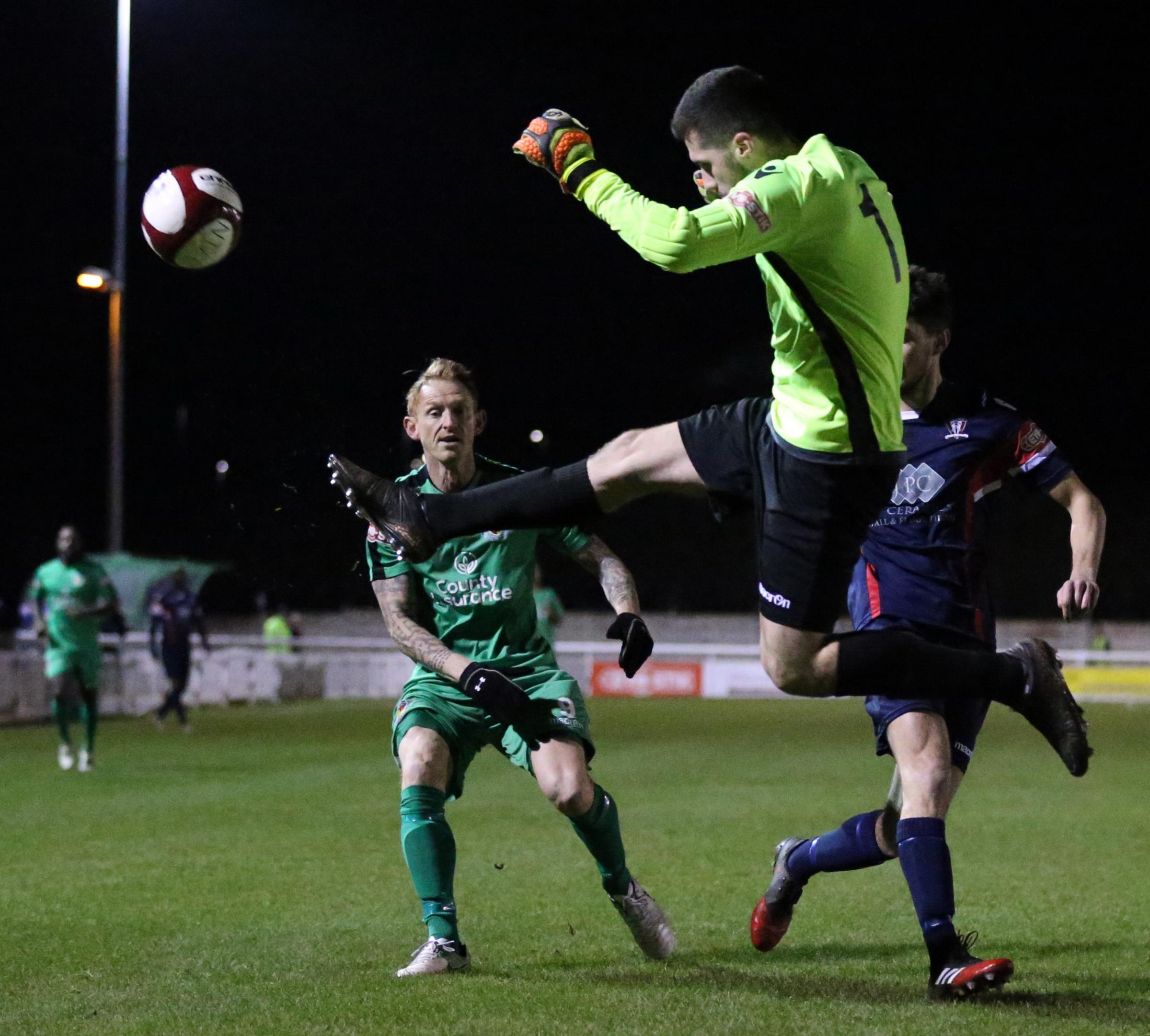 Witton Albion goalkeeper Ryan Neild goes airborne to make a clearance as Nantwich Town's Steve Jones closes in. Picture: Jonathan White