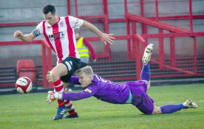 Witton Albion captain Rob Hopley is pulled to the floor by Warrington Town goalkeeper Charles Albinson to concede a penalty during the first-half on Boxing Day. Picture: Karl Brooks Photography