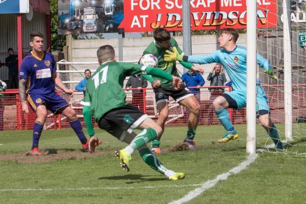 Northwich Guardian: Aaron Smith challenges goalkeeper Ben Ascroft for a ball that he then forced over the line to score a decisive goal for 1874 Northwich in a Macron Cup final victory against City of Liverpool on Saturday. Picture: Ian Dutton